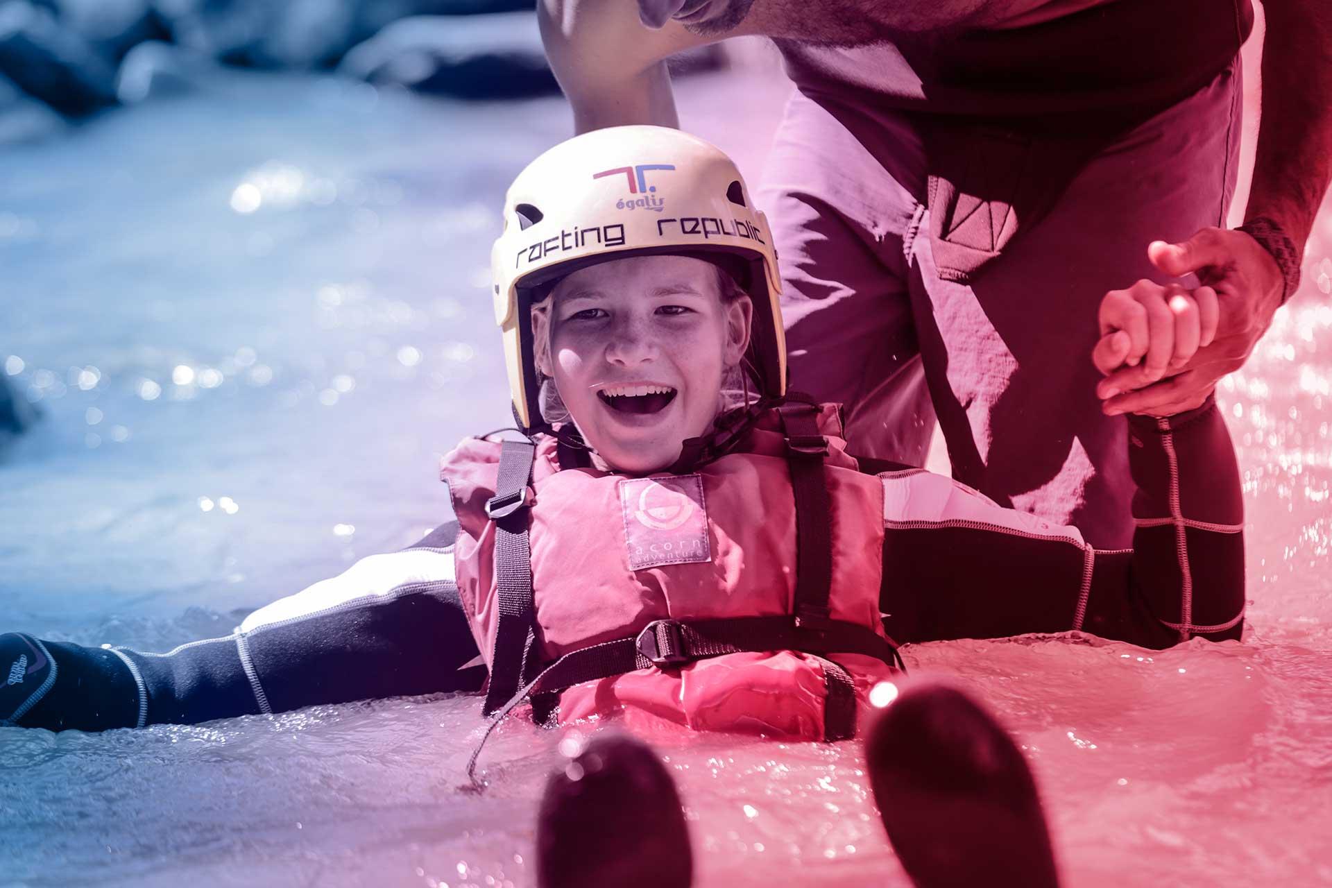 foto di un bambino sorridente vestito da rafting immerso nel fiume