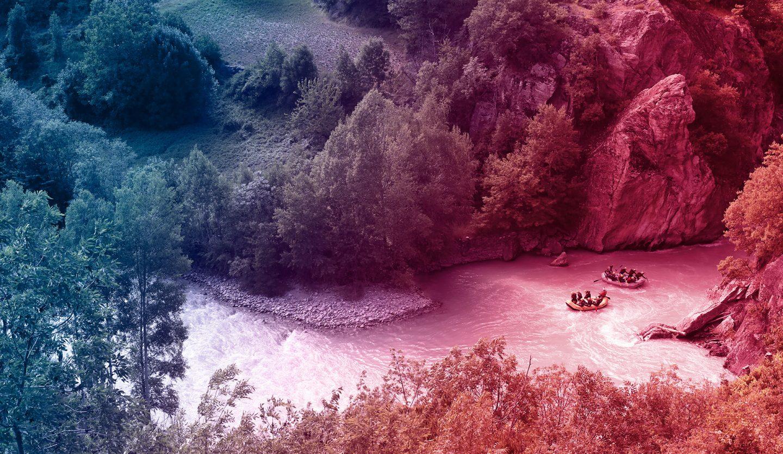 foto del fiume dora baltea che scorre tra gole naturali e due gommoni che la navigano