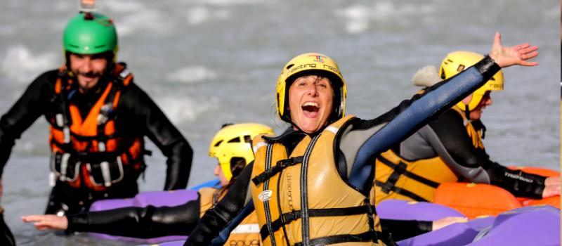 foto di una persona che saluta felice con guida hydrospeed sullo sfondo