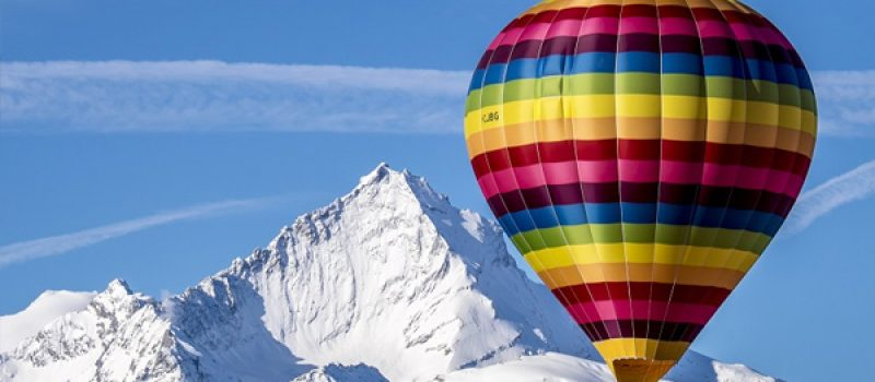 foto di una mongolfiera con sfondo di montagna innevata