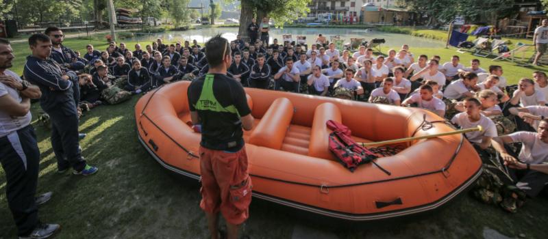 foto di una guida di rafting di spalle che fa un briefing ad un gruppo numeroso davanti ad un gommone