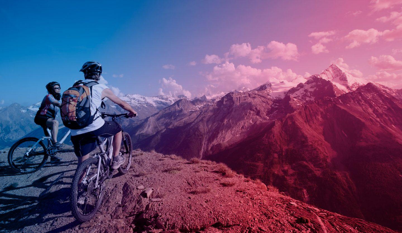 foto di un panorama di motagne con in primo piano una persona in mountain bike