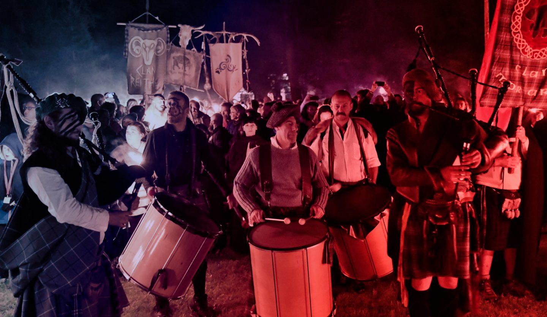 foto di un gruppo di suonatori di tamburo con sullo sfondo bandiere celtiche